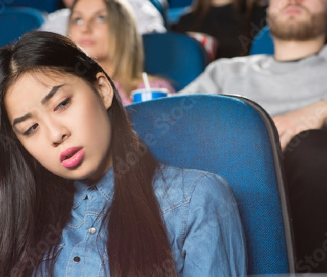 Young Beautiful Asian Female Looking Away Bored Sitting At The Movie