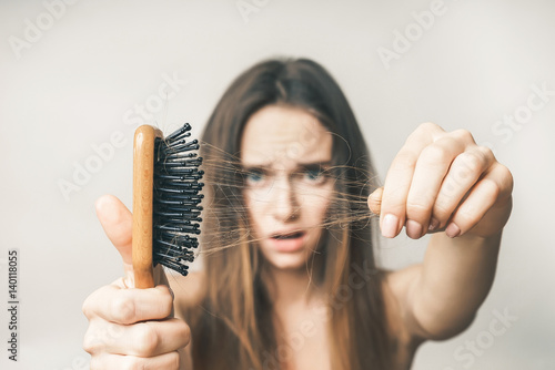 Woman with hair comb loss hairs close up