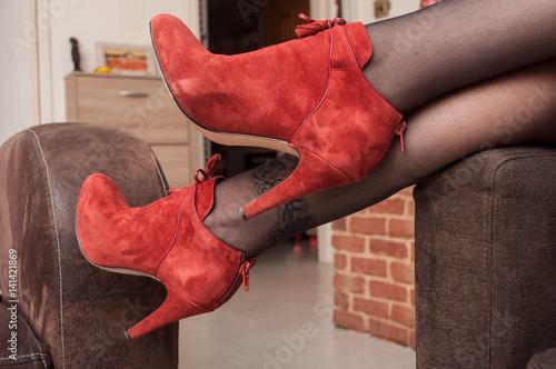 detail jambes de femme allongee dans un canape avec chaussures a talon haut