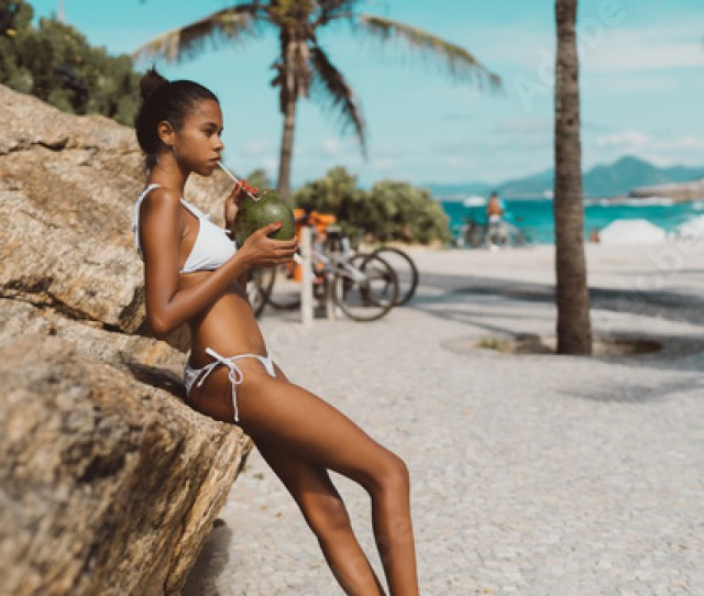 Side View Of Svelte Sexy Brazilian Girl Leaning On The Rock And Holding In Hands Fresh Coconut Young Hot Black Female With Model Body Is Drinking Coco