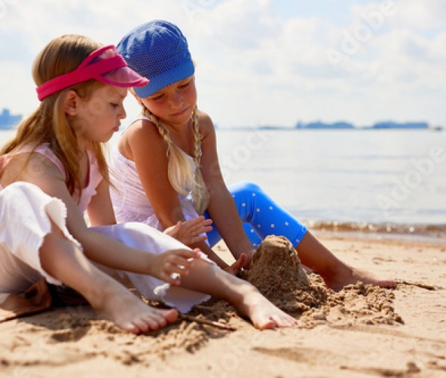 Two Barefoot Girls Sitting On Beach And Building Tower From Sand By Seaside On Summer Day
