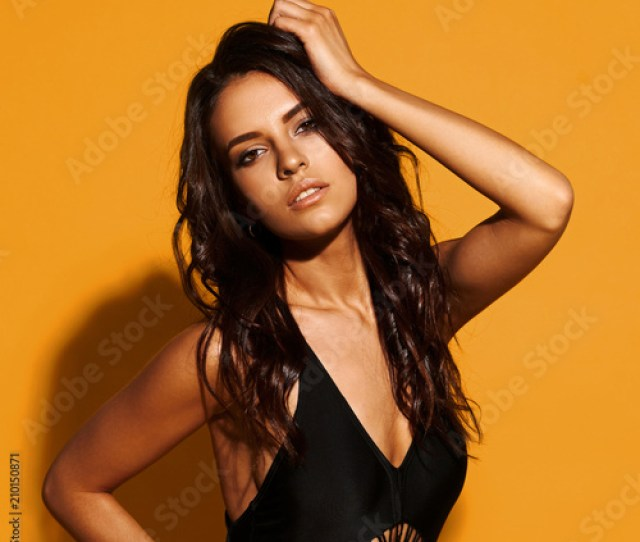 Young Sexy Slim Tanned Woman In Black Swimsuit Posing Against Yellow Background Fashion Portrait Of