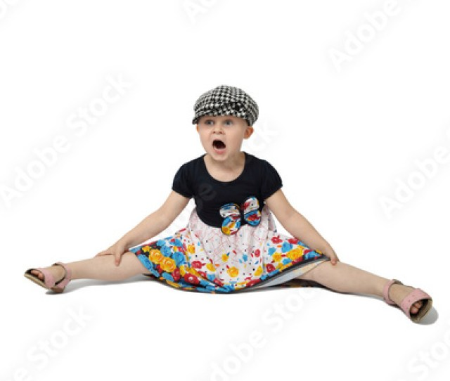 Little Girl In Cap Sits On Floor With Legs Spread Apart And Mouth Open In Astonishment