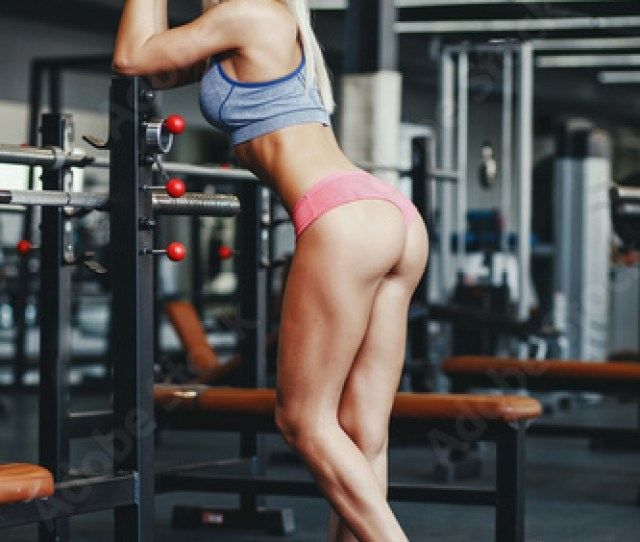 Sexy Fitness Happy Blonde Girl In Sport Wear With Perfect Body In The Gym Posing And