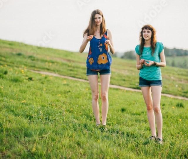 Two Young Lovely Girls With Long Hair And Naked Legs Spending Time At Nature Outdoor