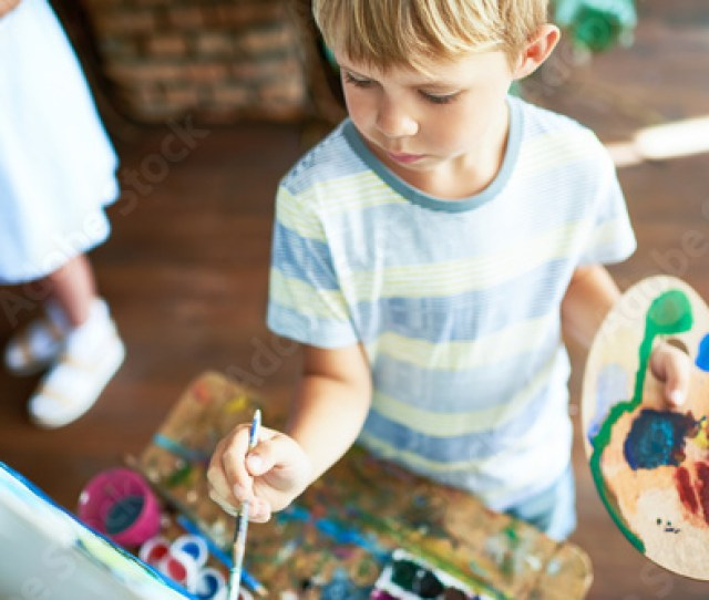 High Angle Portrait Of Cute Blonde Little Boy Painting On Easel During Art Class Concentrating