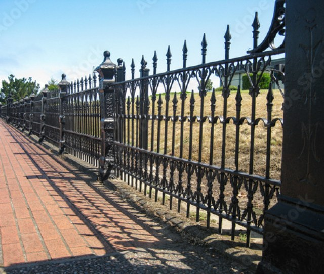 A Perspective View Of An Antique Wrought Iron Fence Borders A Yard Casting Dramatic Shadows On