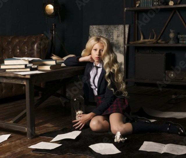 Beautiful Long Haired Blonde Schoolgirl Tiredly Sits On On The Floor At A Table Full Books