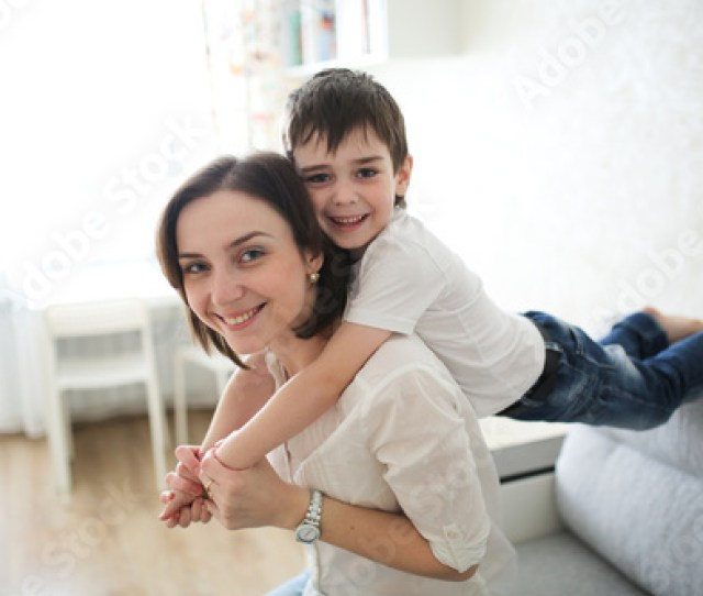 Beautiful Brunette Mom And Son Hugging On Couch