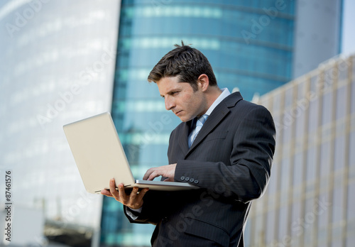 young businessman holding computer laptop working urban business