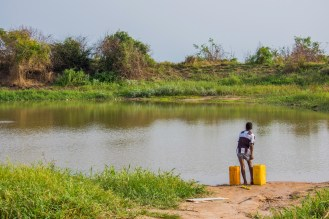 A boy pulls his shorts up so he can walk knee deep into the pond to fetch water