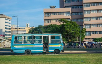 A mass transit bus drives by. In the background is the Ghana Commercial Bank headoffice. Accra,Ghana.