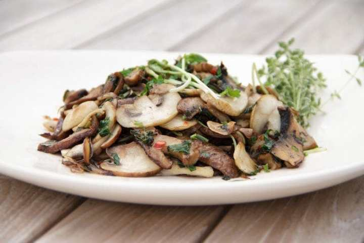 A plate of thinly sliced and cooked mixed mushrooms with ample chilli and fresh herbs on the outdoor dining table
