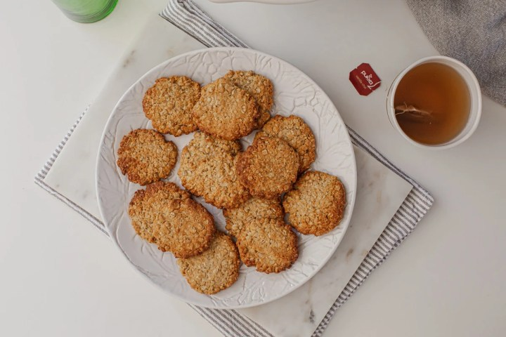 A plate full of freshly baked healthy ANZAC biscuits with a mug of hot frothy chai