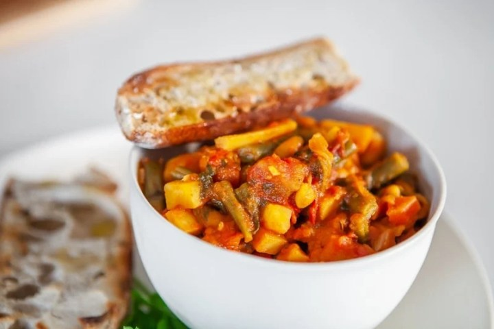 Close up of a bowl of root vegetable stew, with a piece of toasted sourdough balanced over the top