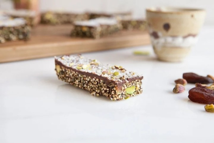 Close up of a protein packed quinoa bar with a chocolate topping, with dried apricots and pistachios beside it