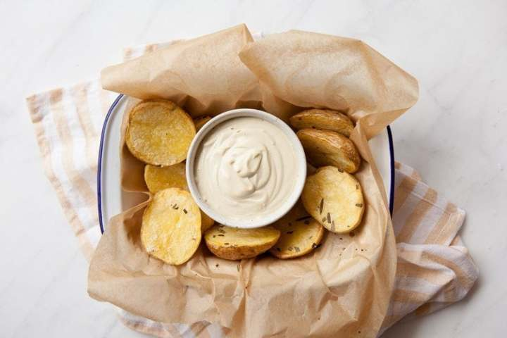 Creamy Vegan Aioli made with Cashews in a ceramic dish, surrounded by roast potatoes