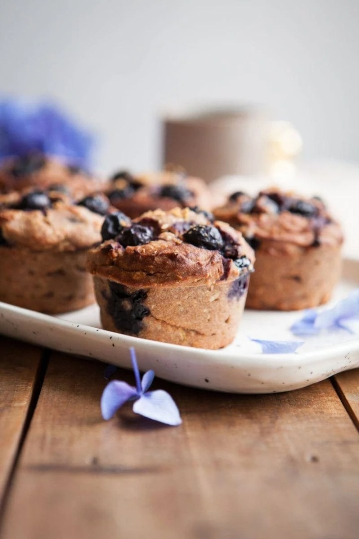 Close up of Gluten Free Blueberry Muffins showing blueberries and lemon zest pressed into the tops