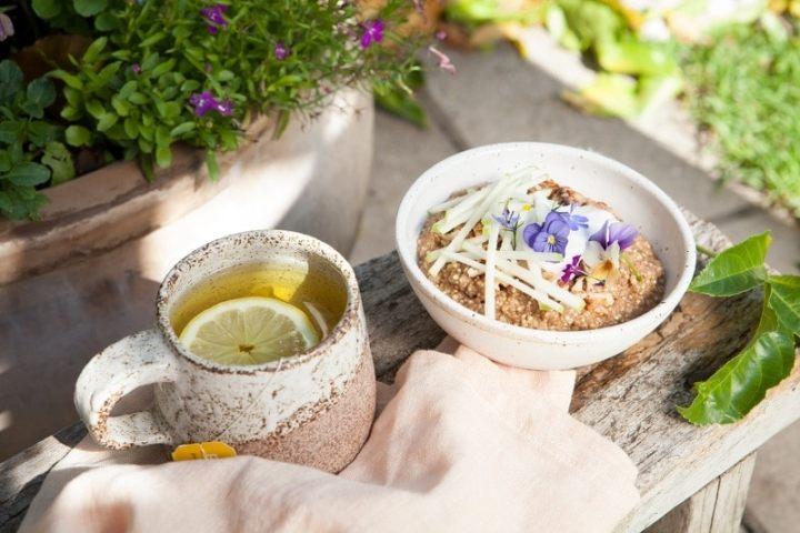 Quinoa Porridge in a bowl with a mug of hot tea in an outdoor garden setting