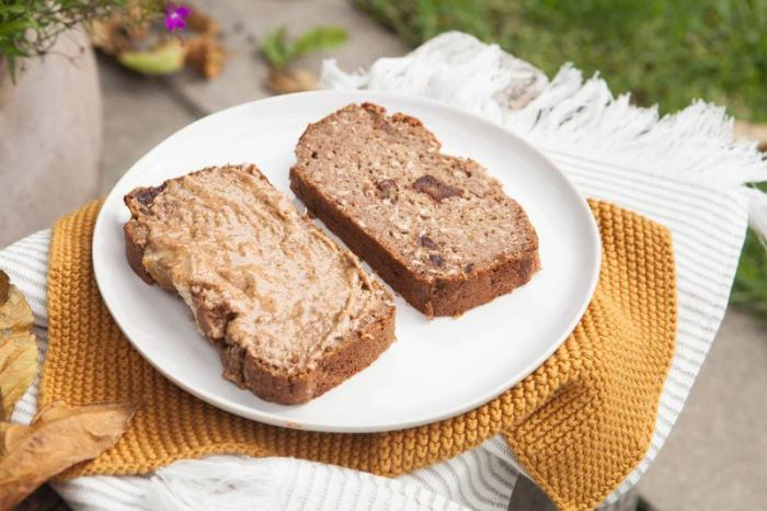 Two slices of gluten free vegan banana bread with almond butter on top, in a garden setting