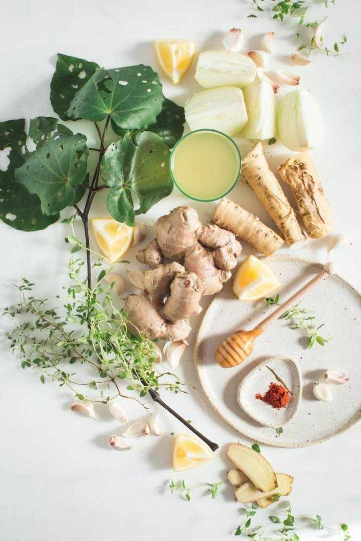 Ingredients for a homemade herbal digestive and immune tonic laid out over the kitchen bench