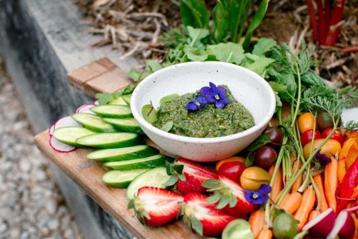 Vegetable platter with pesto on rustic board resting on the edge of a garden bed ready to be enjoyed