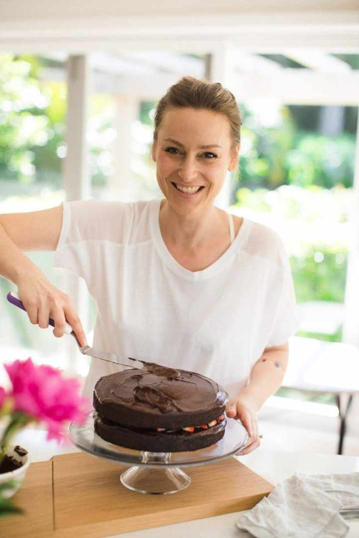 Lauren in the kitchen with a cheesy smile! Frosting the chocolate cake