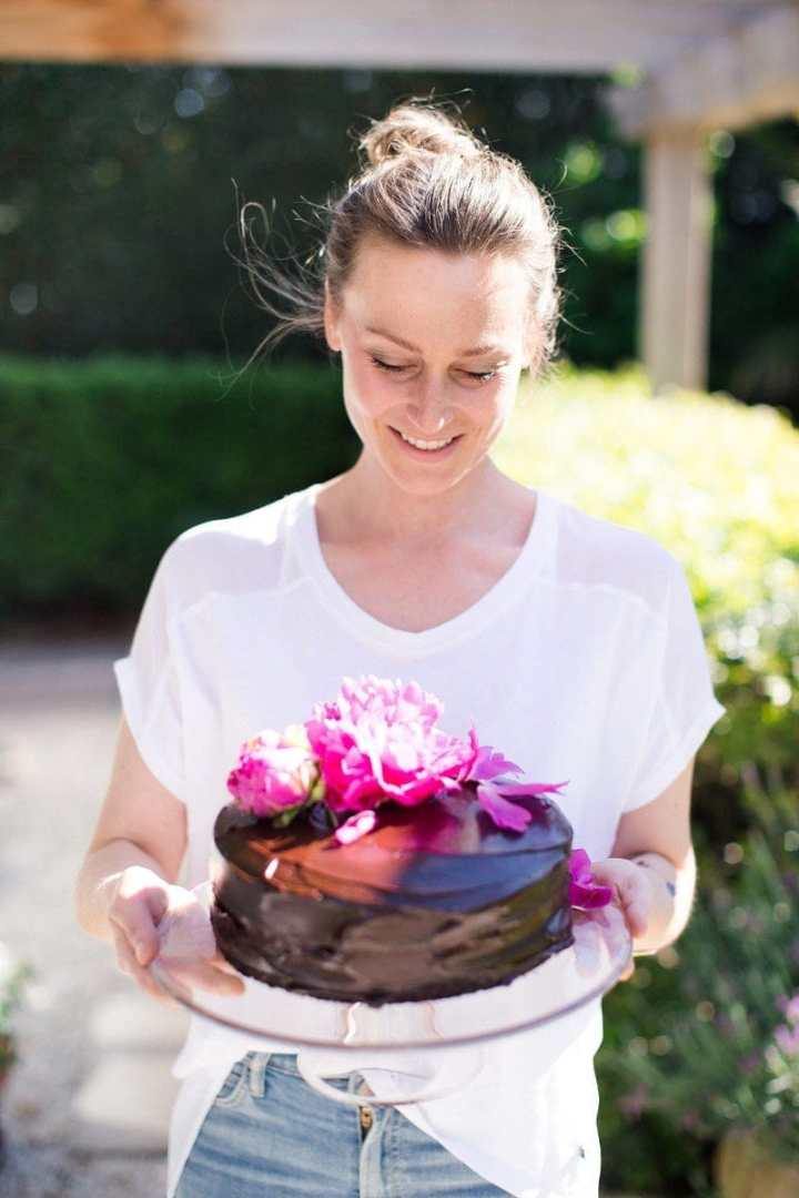 Lauren holding the finished chocolate cake on a glass cake stand outside under the balcony on a nice day