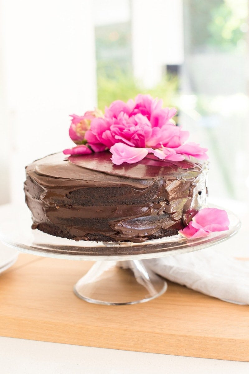 Double layer frosted chocolate cake on a glass cake stand on the kitchen bench