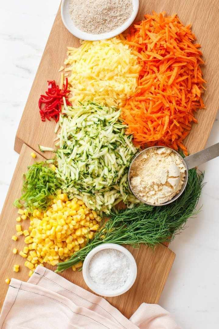 Overhead shot of grated vegan cheese, vegetables and herbs on a chopping board ready to make fritters