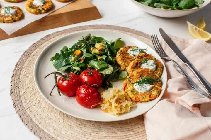 A healthy meal of salad, tomatoes, kraut and vegan fritters on a plant on the kitchen bench