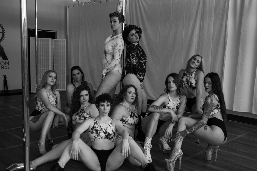 Ten people looking at camera, arranged in a pole dance studio.