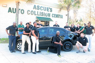 Ascue s Auto Body   Paint Shop   Located in Mt  Pleasant since 1968  Ascue s Auto Collision Center Staff posing by a wrecked car