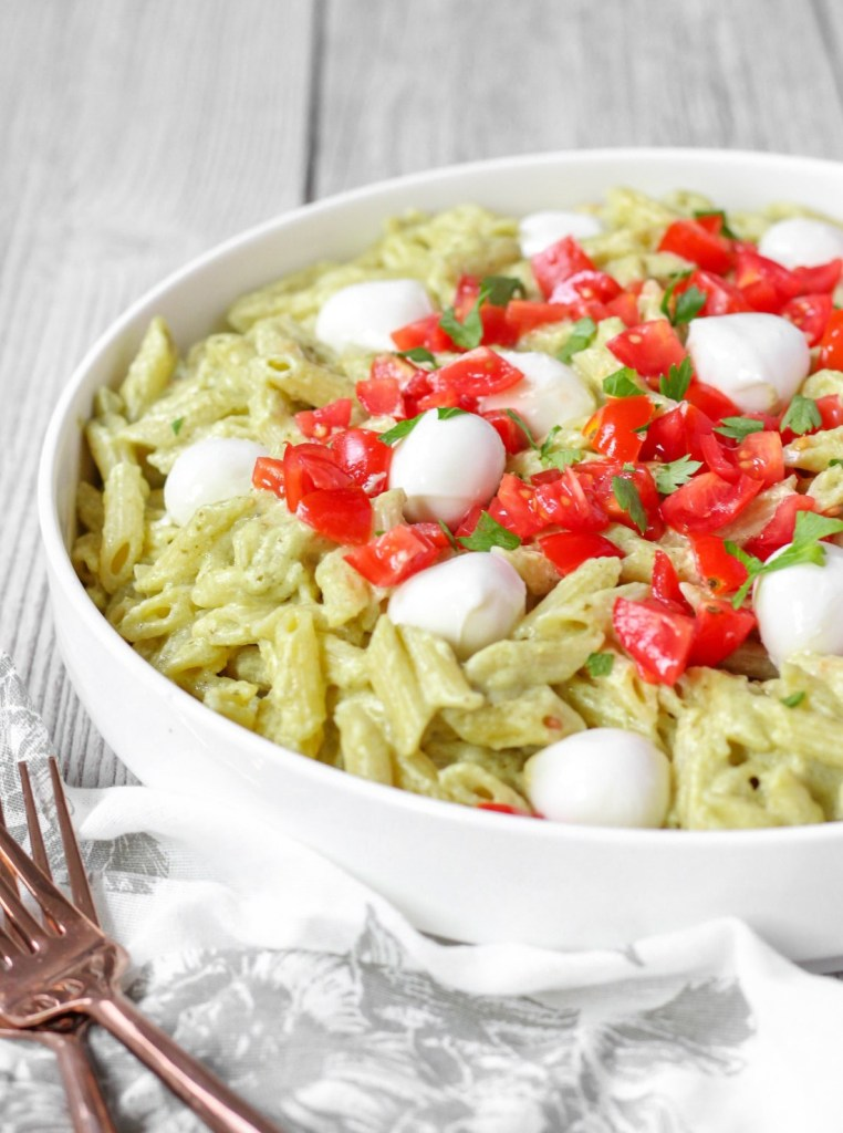 creamy pesto pasta topped with diced tomatoes in a white bowl.