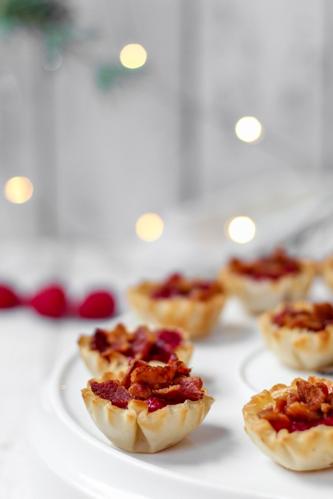 grouping of the phyllo cup appetizers, raspberries and white Christmas lights in the background.