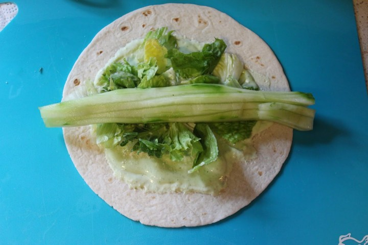 process shot, sliced cucumber on top of the romaine, green goddess dressing, and the tortilla.