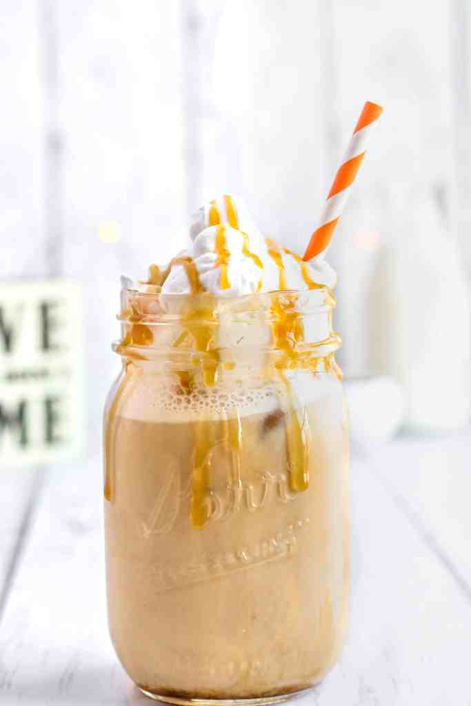 A mason jar of an iced caramel latter with whipped cream and an orange striped straw, caramel drizzled over top the whipped cream and drizzling down the side of the mason jar.