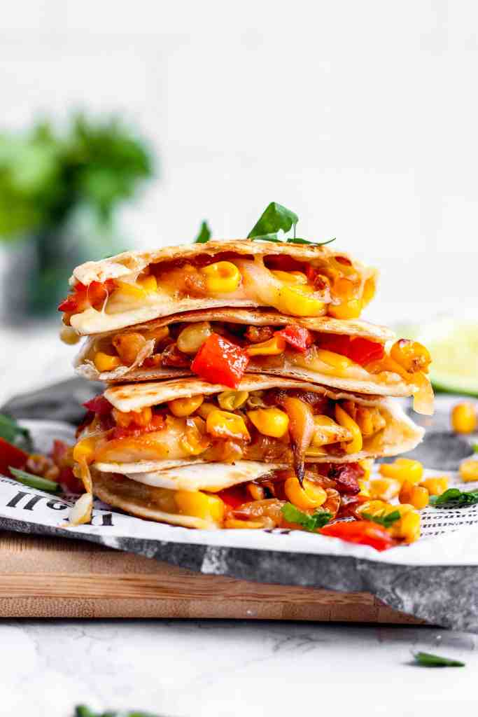 A close shot of a stack of Corn and Red Pepper Vegetarian Quesadillas on a wood board with folded wax paper newspaper. Parlsey in the background.