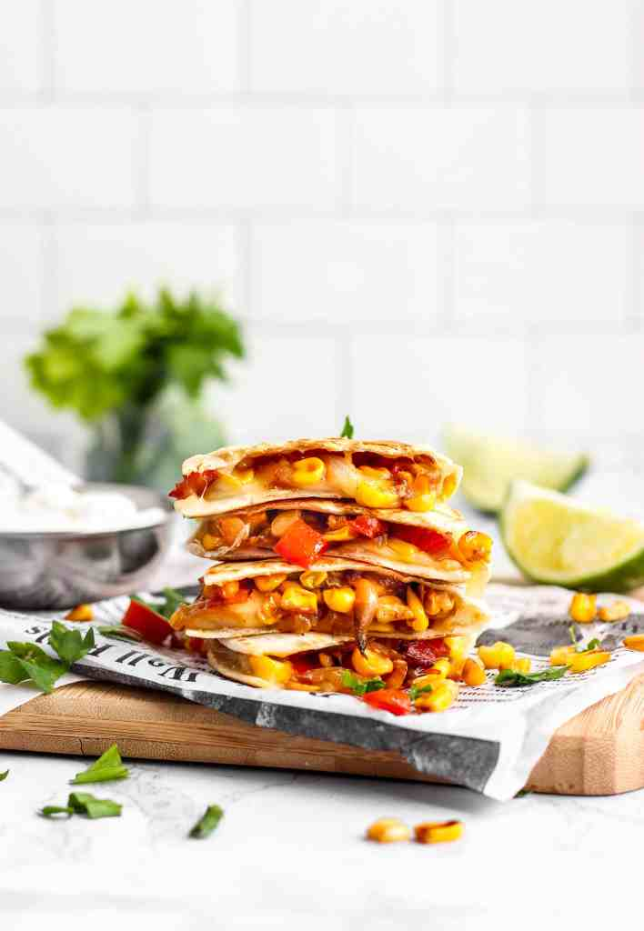 a stack of Corn and Red Pepper Vegetarian Quesadillas on a wood board with folded wax paper newspaper. A small silver bowl of sour cream and parsley and lines in the background with scattered corn kernels throughout.