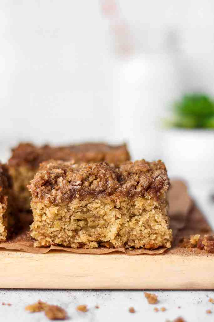 A slice of the banana coffee cake on a wood board with crumbs around it.