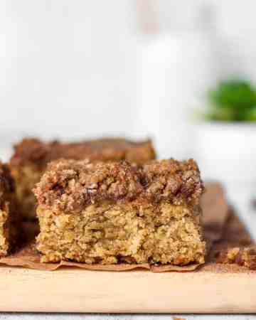 banana coffee cake on a wood board with a glass of milk and succulent in the background
