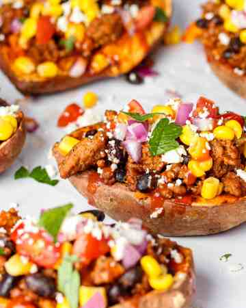 a grouping of Mexican stuffed sweet potatoes on a white marble surface.