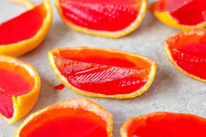 Group of the orange slice jello shots on a light grey board.