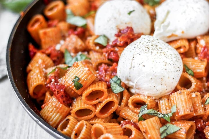 A black pan with the mezzi regatoni pasta and three large balls of burrata cheese.