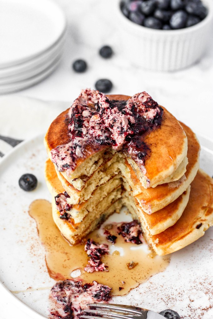 A stack of pancakes with the blueberry butter on top and a slice taken out.