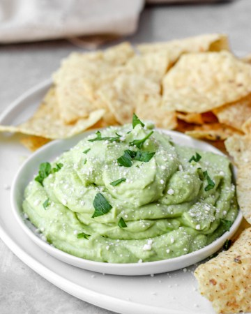 A small round plate with the whipped avocado dip on a plate of chips.