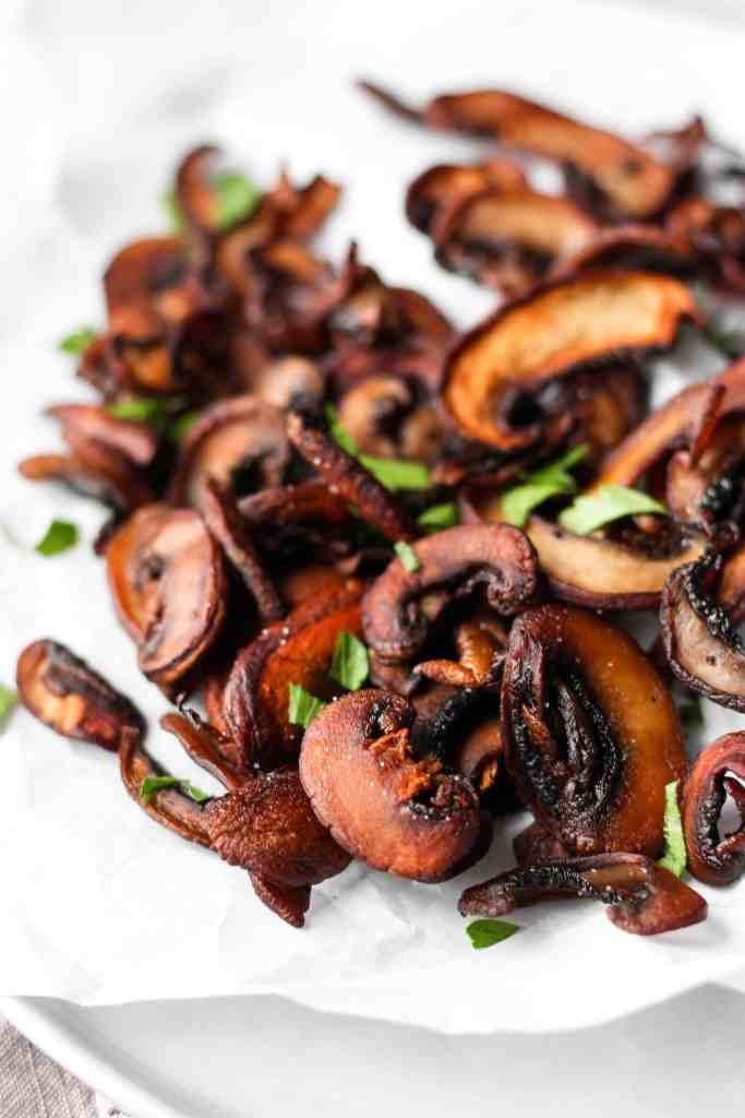 close shot of mushroom chips on a plate with parsley.