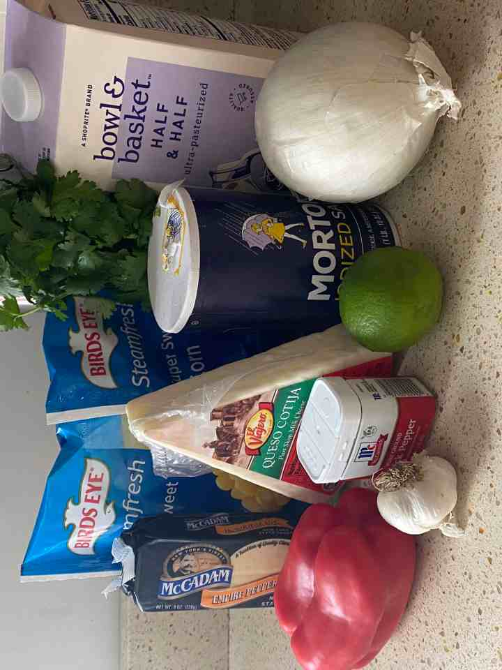 photo of ingredients, missing from here is the chicken broth I forgot it! Corn, pepper jack cheese, Cotika, red pepper, garlic, onion, lime, pepper, salt, half & half, cilantro.