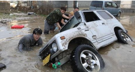 Cars and houses were left wrecked by heavy rains, leaving areas covered in debris and thick mud