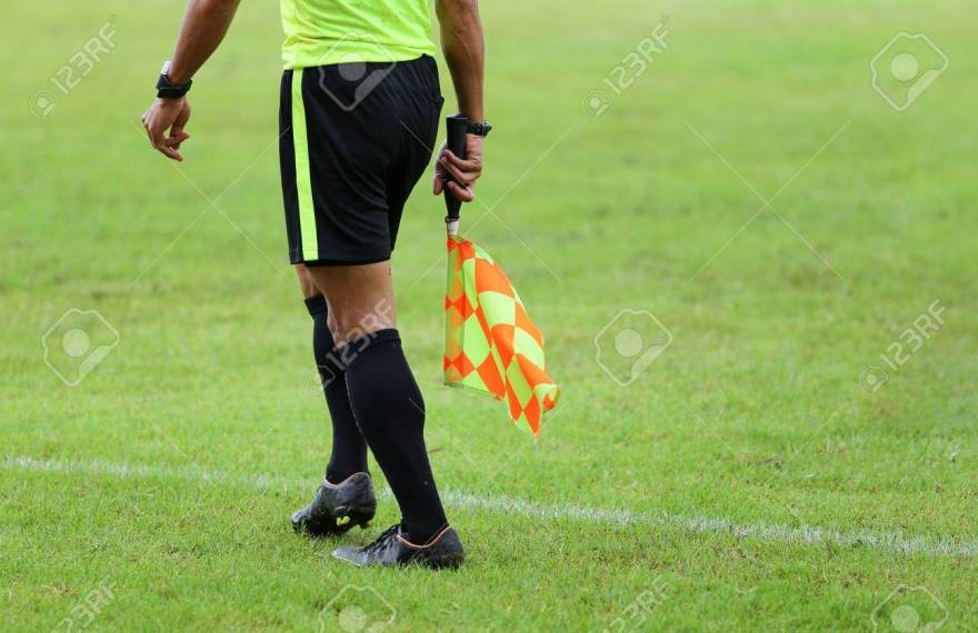 66982863-assistant-referees-signalling-with-the-flag-on-the-sideline-during-a-soccer-match